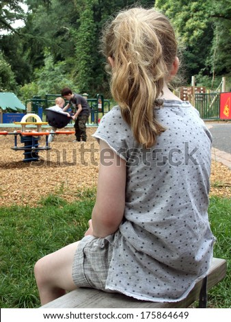 Lonely Girl watching other kids playing - stock photo
