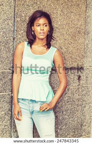 Lonely Girl. Wearing a green tank top, fashionable jeans, drop earrings, a young pretty black woman is standing against the marble wall, sad, thinking, lost in thought. Woman Casual Street Fashion.  - stock photo