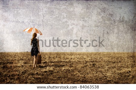 Lonely girl with suitcase and umbrella at countryside field.