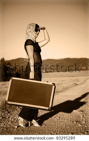 Lonely girl with suitcase at country road.. Photo in old image style. - stock photo