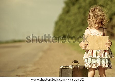 Lonely girl with suitcase standing about road and holding paper with copy space in hands