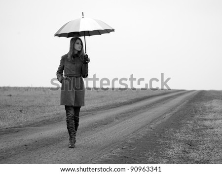 Lonely girl with umbrella at country road. Photo in old black and white style with little noise.