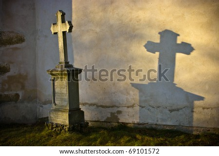 Lonely grave in rays of sunshine - stock photo