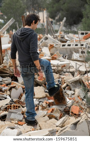 Lonely guy  rummaging  in lots of debris from a pulled down house - stock photo