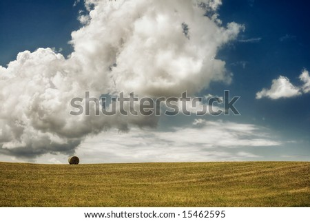 Lonely hay bale in a field under big clouds. - stock photo
