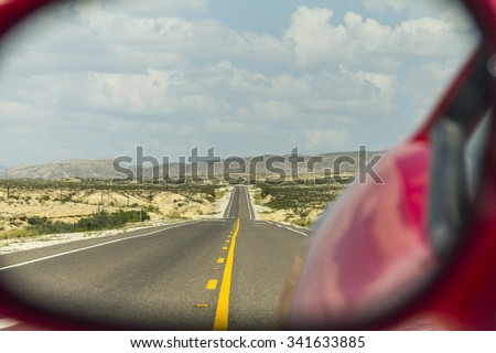 Lonely Highway in Texas seen through rear mirror - stock photo