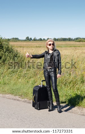 lonely hitchhiker at rural roadside - stock photo