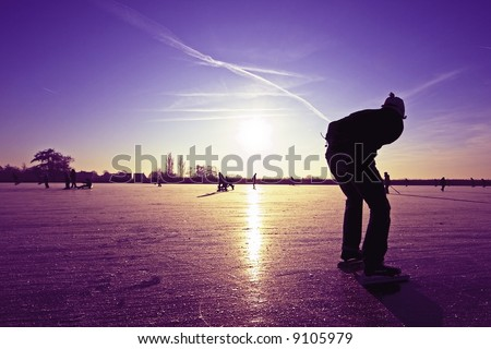 Lonely ice skater at a purple sunset on a lake in the countryside from the Netherlands - stock photo