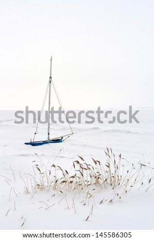 lonely isolated Sailing Boat at german Baltic Sea Coast in Winter - stock photo