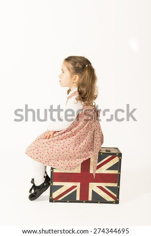 Lonely little girl sitting on a old suitcase and waiting looking aside, isolated on white background - stock photo