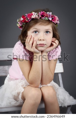 Lonely little girl sitting on the bench - stock photo
