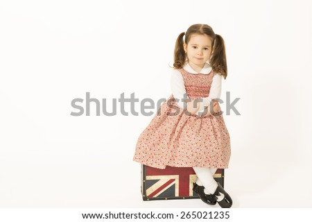 Lonely little girl with old suitcase. Lovely happy little girl sitting on a old suitcase waiting, studio shot on white background - stock photo