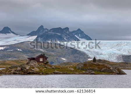 lonely little wood house near glacier - stock photo