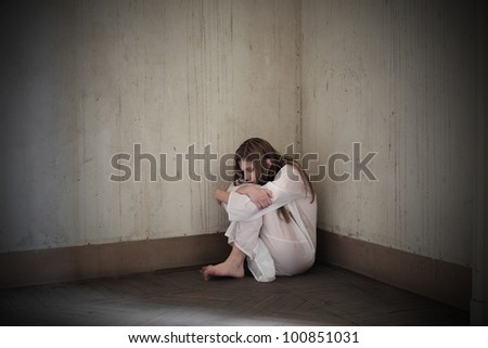 Lonely mad woman sitting in the corner of a room - stock photo