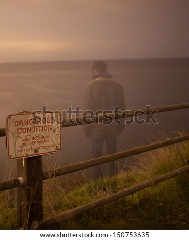 Lonely male standing on top of a cliff edge - stock photo