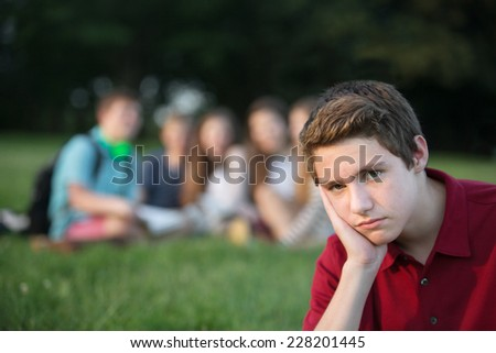 Lonely male teenager sitting with hand on cheek - stock photo