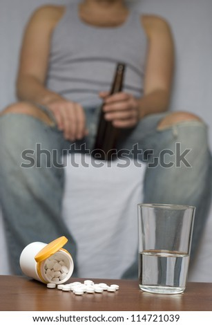 Lonely man alone at home. Drugs on the table. Dark, out-of-focus background. - stock photo