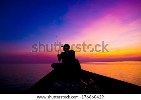 Lonely man fishing silhouettes on sunset sky beautiful lagoon - stock photo