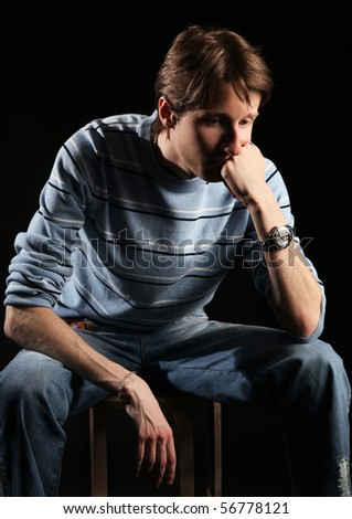lonely man in blue sweater sitting on chair - stock photo