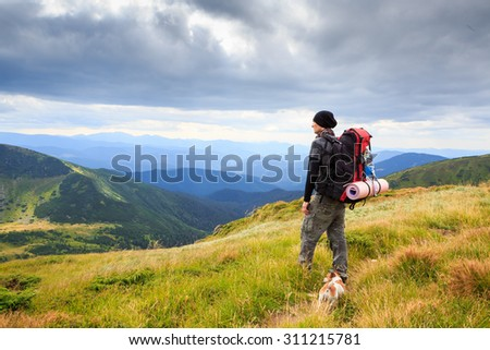 Lonely man in the mountains, hike dog looks wistfully at a lovely mountain landscape. Series of photos. Dramatic cloudy sky.