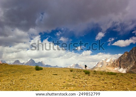 lonely man in the mountains with clouds on the blue sky - stock photo