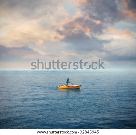 Lonely man on a boat in the middle of the sea - stock photo