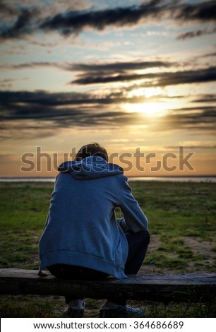Lonely Man on the Nature at Sunset with the Sun in the Background - stock photo