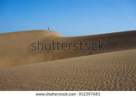 Lonely man Reaching the peak of a large dune in a desert under blue sky /  Large sandy dunes in a wide dessert / Southbeach of Gran Canaria