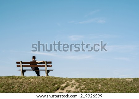 lonely man siting on a bench on an empty landscape