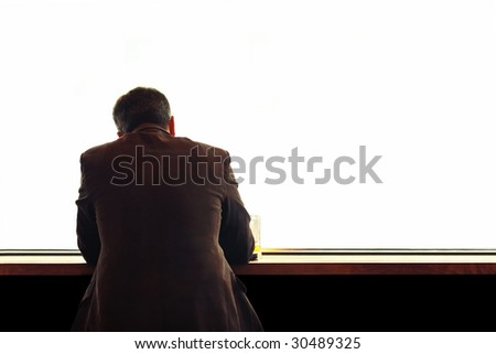 lonely man sitting at the table - stock photo