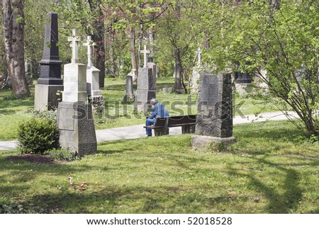 Lonely Man Sitting In a Cemetery - stock photo