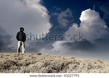Lonely man stand and watch on the hill with dramatic heaven. - stock photo