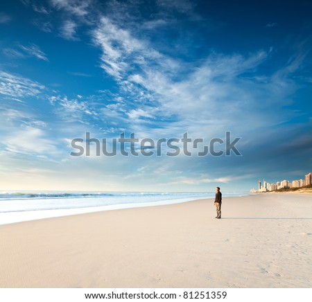 lonely man stands on the beach looks towards the sun light (gold coast, Queensland, Australia) - stock photo