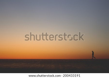 lonely man walking alone on the horizon line in an empty landsca - stock photo