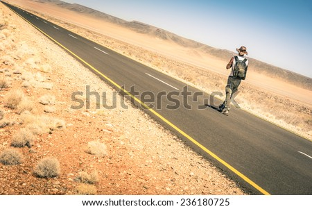 Lonely man walking along the road among the namibian african desert - Concept of alternative lifestyle - Travel trip adventure around the world - stock photo