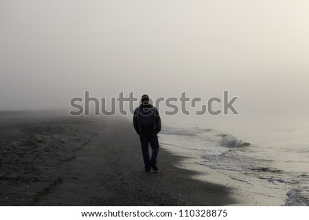Lonely man walking on a foggy beach - stock photo