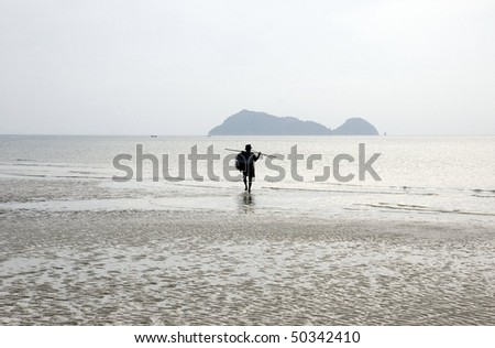 lonely man walking on the beach late afternoon, Thailand - stock photo