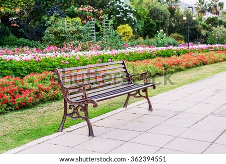 Lonely metal bench in the flower garden - stock photo