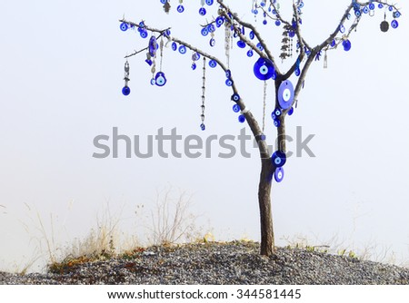 Lonely naked tree decorated with traditional turkish symbol - blue eye, Nazar Boncugu, made of glass against the background of heavy white fog in Goreme, Cappadocia, Central Anatolia, Turkey - stock photo