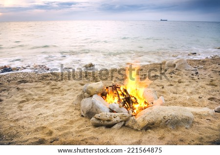 Lonely night fire on seacoast in the autumn - stock photo