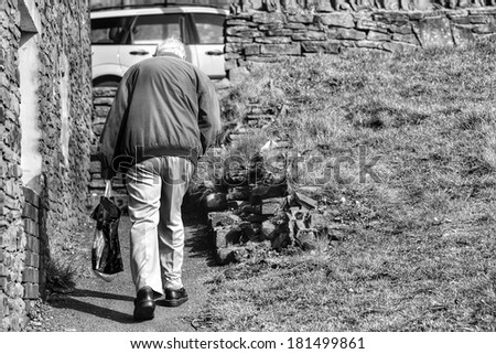 Lonely old man climbing steps. - stock photo