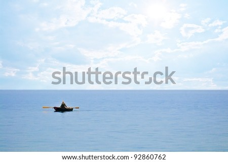 Lonely old man in the rowing boat on the sea - stock photo