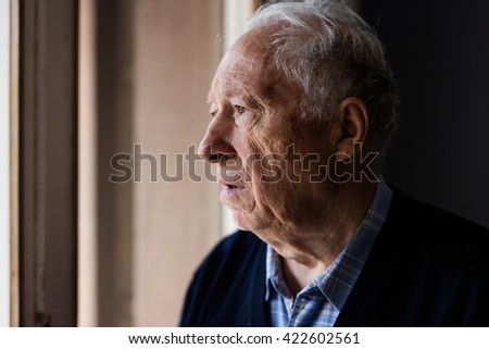 Lonely old man staring out of a window  - stock photo