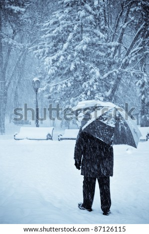 lonely old man with umbrella walking under the snow, selenium toned - stock photo