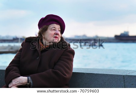 Lonely old woman looks at the sea - stock photo