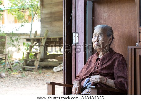 Lonely old woman sitting by the door in his cottage. - stock photo