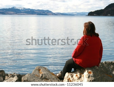 Lonely overweight woman looking at the ocean - stock photo