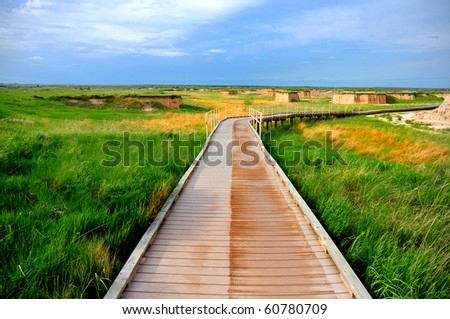 Lonely path on green field at Badlands national park, South Dakota - stock photo