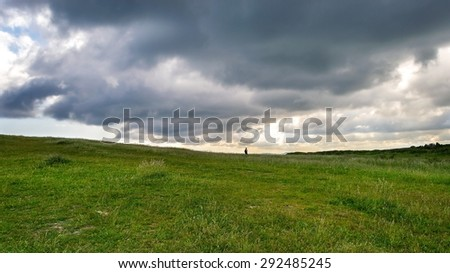 Lonely person walking in the meadow under the clouds - stock photo