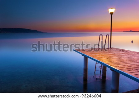 Lonely pier at sunset. Garda lake - stock photo
